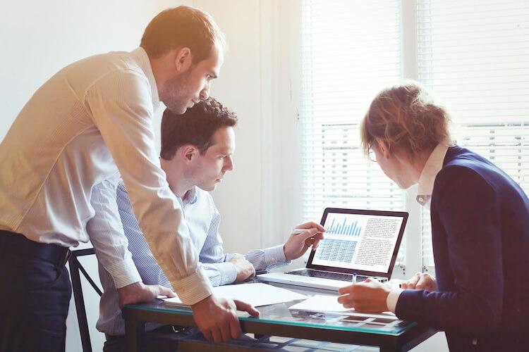 Business executives analyzes data charts from their previous quarter.