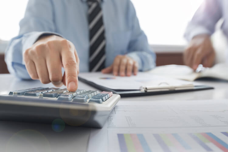 An accountant uses a calculator to calculate costs for a client.