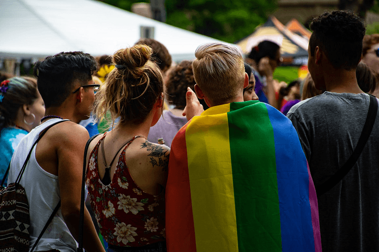 Group of youths, one of whom is wearing an LGBTQ flag.