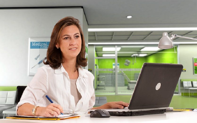 health care admin working on a laptop in a hospital