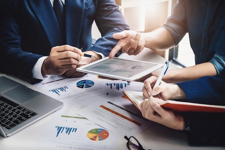 Business associates analyze their company's previous quarter's data.
