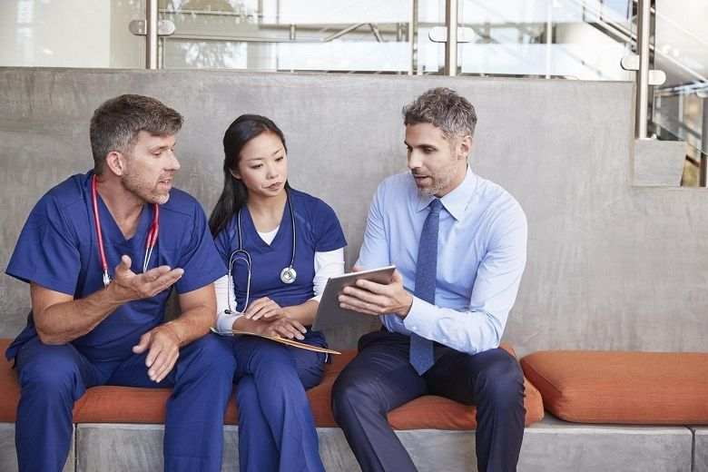Healthcare leader discusses information on a tablet with colleagues.