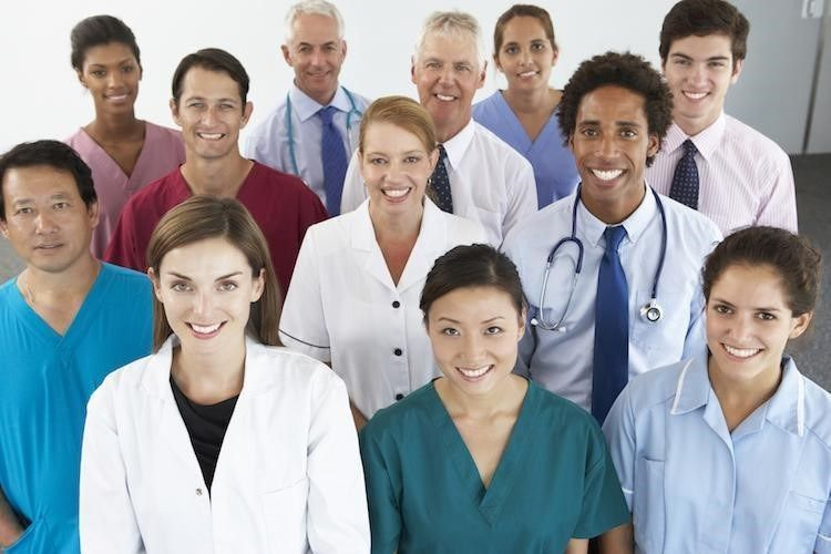 Diverse public health workers pose together in a group in scrubs and business attire.