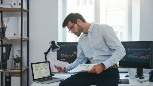 A male professional sits on a desk while looking at documents