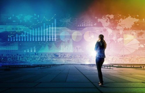 A lady standing in a virtual world of data analytics graphics