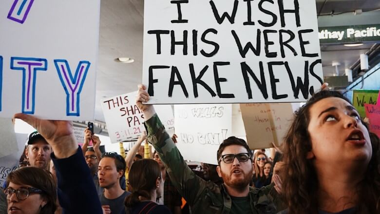 "People protesting in an airport as man holds up a sign reading, ""I wish this were fake news"""