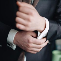 Man in suit holding cufflinks