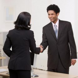 Business-dressed woman and man shaking hands