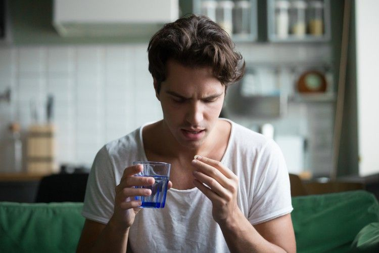 A young man considers taking a pain pill with a glass of water.