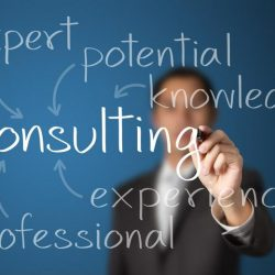 Consulting-related words written on see-through board in foreground relating to consulting by businessman in background
