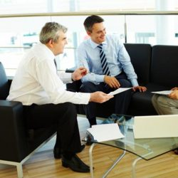 Two businessmen and businesswoman discussing work while seated in a reception area.