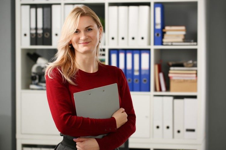A medical services manager stands in front of a shelf of medical records.