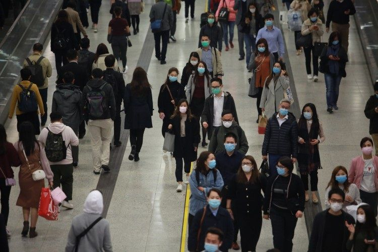 Crowds of pedestrians wearing protective masks pass through a busy transit station in Hong Kong.