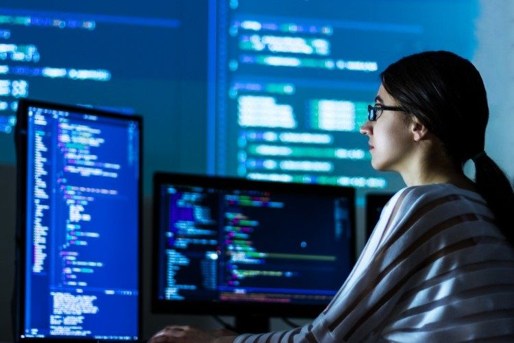 A software developer works in front of two displays showing code.