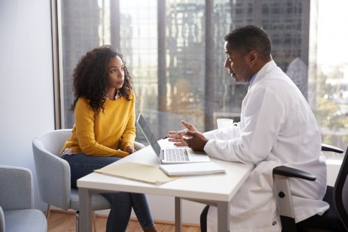 Women discussing her health with a health care profession in his office.
