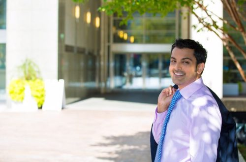Young professional smiling with sport coat flung over shoulder