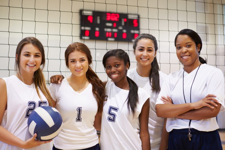 A women's high school volleyball team with their coach.