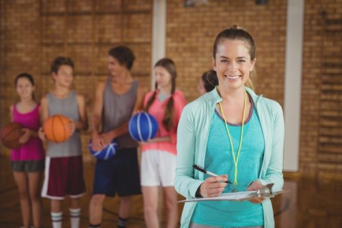 A smiling woman in athletic clothing stands holding a clipboard in front of a group of students on a basketball court.