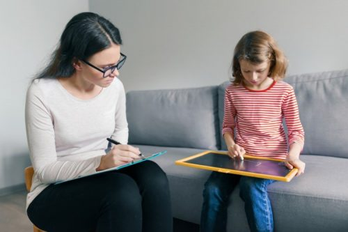A behavioral scientist takes notes on a clipboard while sitting with a troubled-looking child playing with a toy chalkboard.