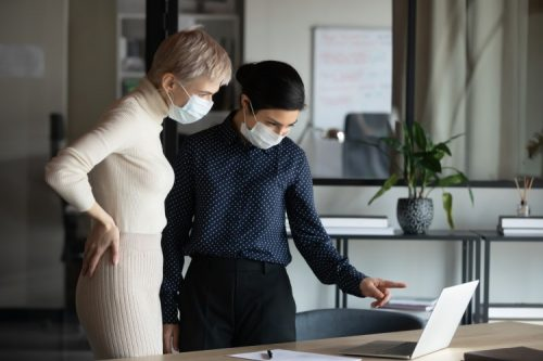 Two women wearing medical protective masks stand next to a laptop in an office; one of them points to the screen.