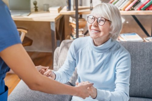 An elderly woman speaks with a caregiver.