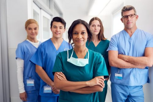 A group of five multicultural male and female nurses wearing scrubs look calmly at the viewer.