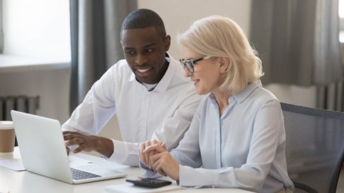 Two corporate accountants work together at a computer
