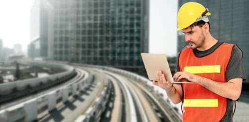 A transportation engineer is consulting plans on a laptop at a work site.