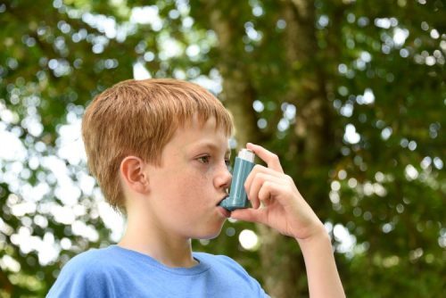 A young child uses an asthma inhaler.