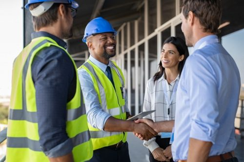 A construction manager shakes hands with a client on a jobsite