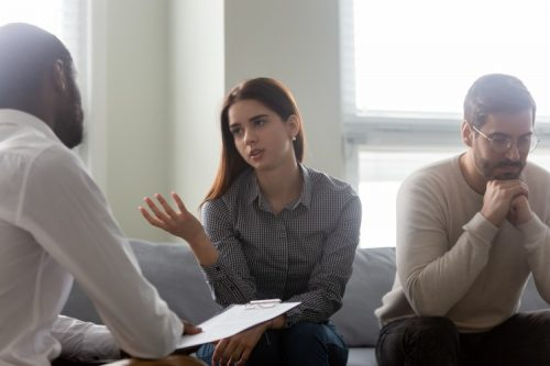 A marriage and family therapist counsels a young couple.