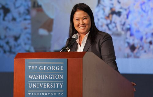 Woman stands at GW podium and smiles