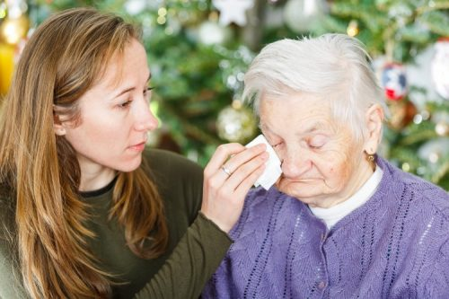 A social worker comforts and counsels a victim of elder abuse.
