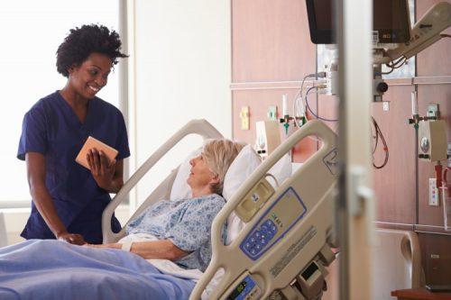 A hospital nurse checks on her patient.