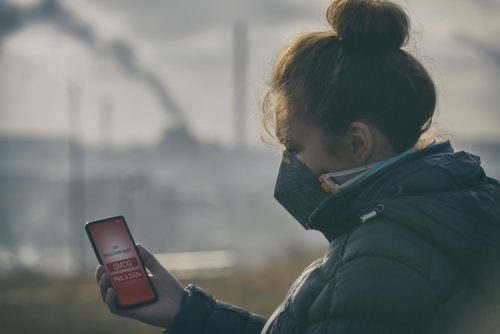 Women wearing a medical mask, holding a phone showing a smog alert.