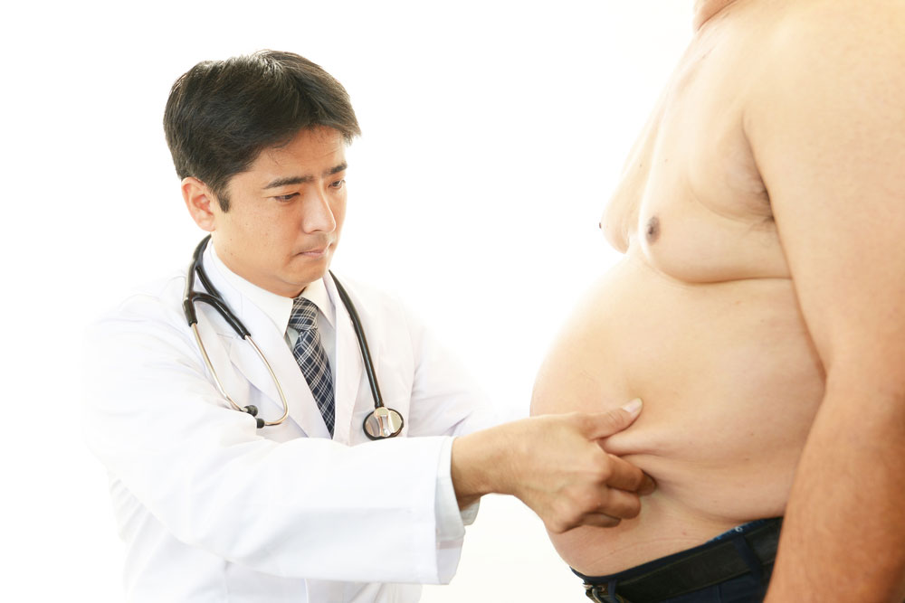 A doctor assessing a mans waist.
