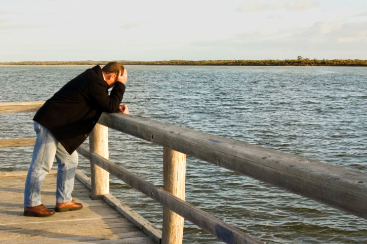 A man standing on a pier holding his head in his hands