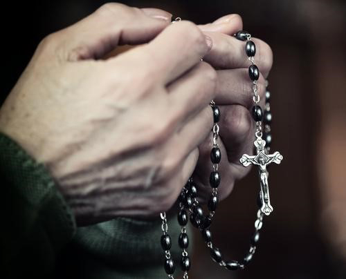 Woman clutching rosary beads