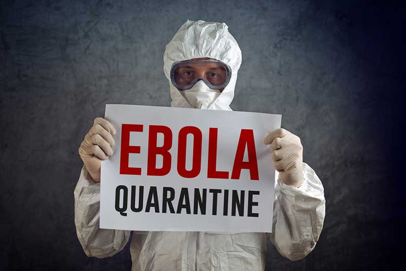 A man in a hazmat suit holding a sign that reads: Ebola Quarantine