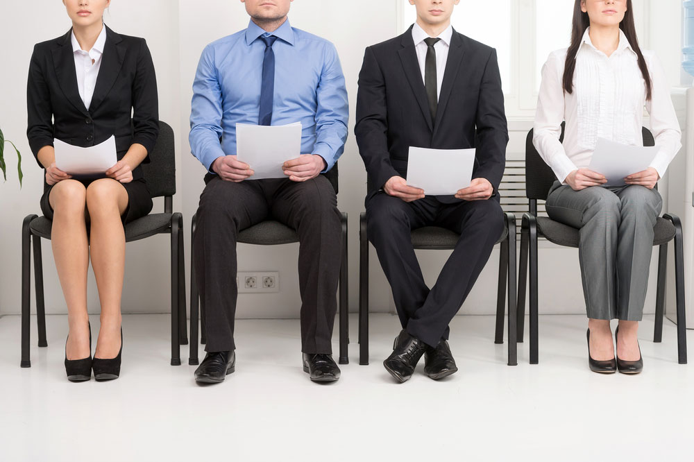 Two men and two women waiting for a job interview