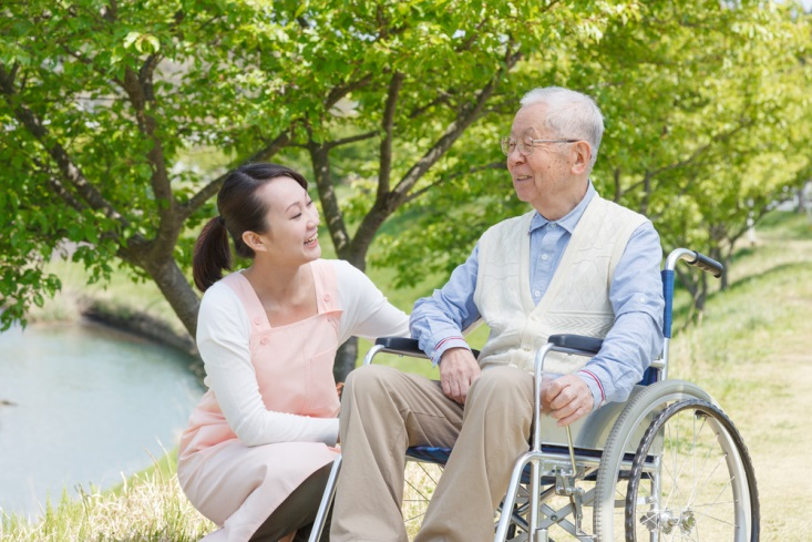A care giver helping a senior person in the park