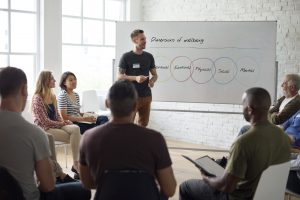 A man stands in front of a whiteboard with Venn diagrams while speaking to a group of individuals seated in chairs.