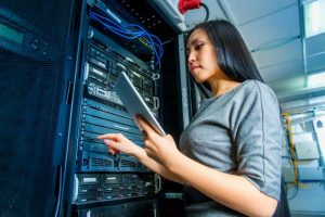 Girl in server room with laptop