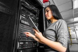 Young woman holding a tablet standing next to server equipment.