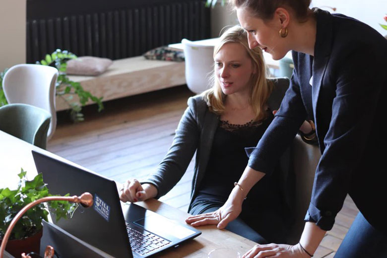 A young female accountant is working at a laptop, while a mentor, also a woman, stands next to her and offers guidance.