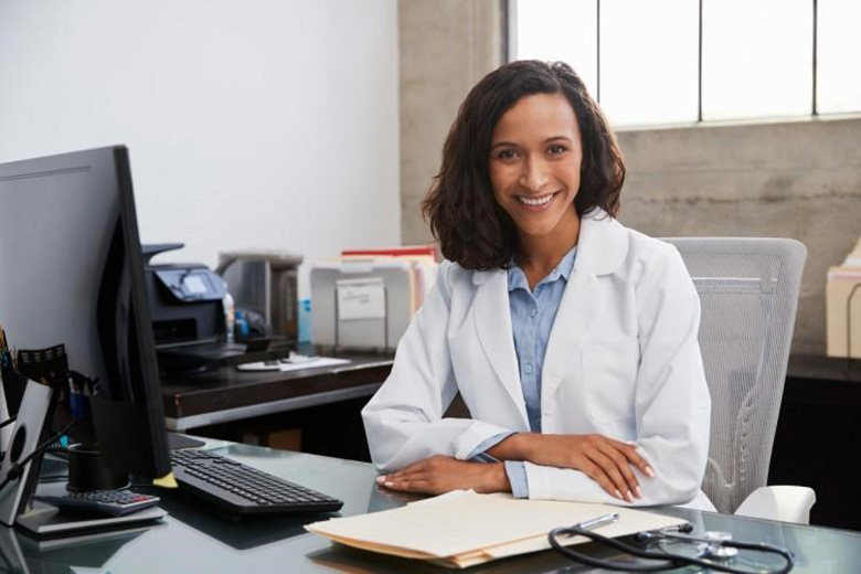 A smiling public health nurse working at her desk.