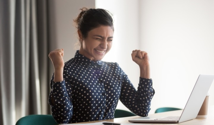 A happy young woman is celebrating after receiving an email notification that she passed the CPA Exam.