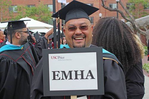A student graduates with his EMHA degree.