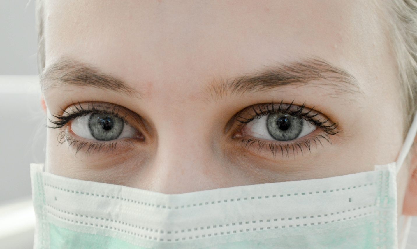 A health care worker wears a mask.