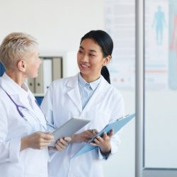 A director of patient safety talks with a doctor.